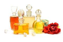 葡萄酒瓶与玻璃塞子、老化妆粉末和人为长毛绒红色玫瑰的香水在白色 免版税库存图片