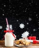 葡萄酒瓶与红色丝带的牛奶和在木桌上的圣诞老人曲奇饼在黑背景 免版税库存图片