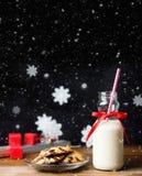 葡萄酒瓶与红色丝带的牛奶和在木桌上的圣诞老人曲奇饼在黑背景 图库摄影