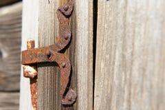 葡萄酒生锈了金属在被风化的木墙壁的门折页 图库摄影