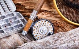 葡萄酒用假蝇钓鱼成套装备和齿轮在岩石和木背景 库存图片