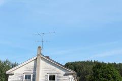 葡萄酒电视天线附加在一个老房子的一个煤渣砌块烟囱 免版税库存照片