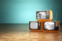 葡萄酒电视概念 堆在绿色backg的减速火箭的电视机 免版税库存图片