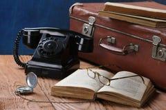 葡萄酒电话、手提箱、手表和旧书 免版税库存图片