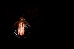 葡萄酒白炽光在黑色的电灯泡细丝 免版税库存图片