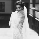 葡萄酒白色礼服pos的华美的愉快的微笑的深色的新娘 免版税库存照片