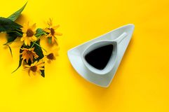 葡萄酒白色陶瓷杯子用咖啡 与延命菊花的创造性的背景在年的黄色纹理颜色的2019年 库存图片