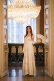 葡萄酒的年轻红发妇女18件世纪礼服在豪华舞厅使用爱好者 免版税库存图片