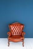 葡萄酒皮革豪华棕色扶手椅子经典布朗皮革沙发和老蓝色背景 库存图片