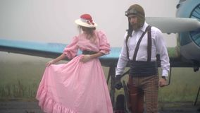 葡萄酒盔甲的一名飞机飞行员和一件桃红色礼服和一个白色帽子的一个女孩在雾的飞机附近站立,慢 影视素材
