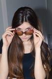 戴葡萄酒眼镜的可爱的小姐 免版税库存照片