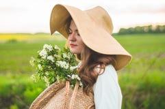 葡萄酒礼服和草帽的美丽的年轻微笑的妇女在领域野花 女孩拿着与花的一个篮子 库存图片