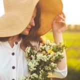 葡萄酒礼服和草帽的美丽的年轻微笑的妇女在领域野花 女孩拿着与花的一个篮子 免版税库存图片