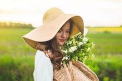 葡萄酒礼服和草帽的美丽的年轻微笑的妇女在领域野花 女孩拿着与花的一个篮子 库存照片