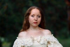 葡萄酒礼服灰棕色的美丽的妇女 长的礼服的逗人喜爱的女孩走在杉木森林里的女王/王后的样式 免版税库存图片