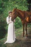 葡萄酒礼服的妇女有马的 免版税库存照片