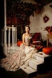 葡萄酒礼服的少妇在秋天门廊 fa的秀丽女孩 免版税图库摄影