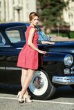 葡萄酒礼服的美丽的少妇有减速火箭的汽车的 免版税库存照片