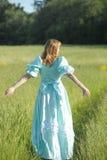 葡萄酒礼服的美丽的金发碧眼的女人去,回到照相机 免版税库存图片
