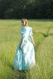 葡萄酒礼服的美丽的金发碧眼的女人去,回到照相机 免版税库存照片