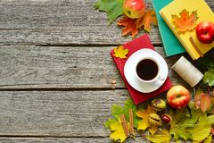 葡萄酒秋天桌用苹果、下落的叶子、葡萄酒书、在老木桌上的咖啡或茶 免版税图库摄影