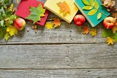 葡萄酒秋天桌用苹果、下落的叶子、葡萄酒书、在老木桌上的咖啡或茶 免版税库存照片