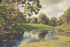葡萄酒秋天视图的样式图象在公园和池塘晴朗的 免版税库存图片