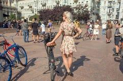 葡萄酒站立与自行车的夏天礼服的少妇在室外节日前 图库摄影