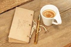 葡萄酒笔记薄、金黄钢笔和杯在木头的浓咖啡 免版税库存照片