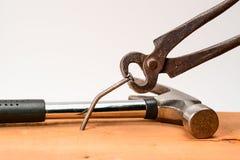 葡萄酒粗砺的伪造的钳子拉扯从委员会弯曲的一个大钉子 使用锤子在背景中 免版税库存图片