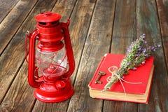 葡萄酒红色灯笼和红色书在木桌上 免版税库存图片