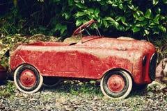 葡萄酒红色玩具汽车在庭院里 免版税库存照片