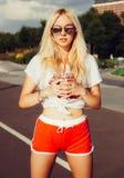 葡萄酒红色短裤和白色T恤杉的美丽的性感的白肤金发的女孩,握两只手每杯新凉快的夏天饮料 夏天v 库存图片