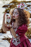 葡萄酒红色礼服的美丽的女孩有玫瑰的 图库摄影