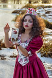 葡萄酒红色礼服的美丽的女孩有玫瑰的 库存照片