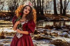 葡萄酒红色礼服的美丽的女孩有玫瑰的 免版税库存照片