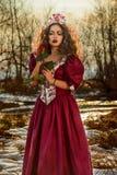 葡萄酒红色礼服的美丽的女孩有玫瑰的 免版税库存图片