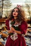 葡萄酒红色礼服的美丽的女孩有玫瑰的 库存图片