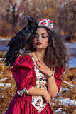葡萄酒红色礼服的美丽的妇女有黑色的 免版税库存图片