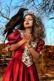 葡萄酒红色礼服的美丽的妇女有黑色的 库存图片
