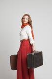 葡萄酒红色裙子的妇女带着手提箱 库存照片
