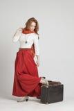 葡萄酒红色裙子的妇女带着手提箱 图库摄影