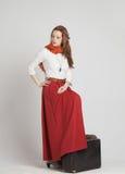 葡萄酒红色裙子的妇女带着手提箱 库存图片