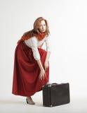葡萄酒红色裙子的妇女带着手提箱 免版税库存图片