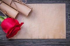 葡萄酒纸在木背景滚动红色有气味上升了 库存图片
