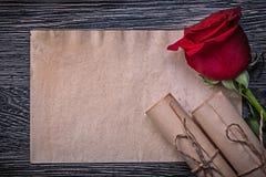 葡萄酒纸在木背景滚动红色玫瑰 免版税图库摄影