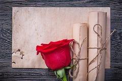 葡萄酒纸在木背景滚动红色芳香上升了 库存图片