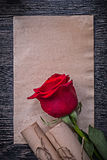 葡萄酒纸在木滚动红色玫瑰花蕾 免版税库存图片