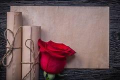 葡萄酒纸在木滚动红色芳香玫瑰花蕾 库存照片