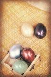 葡萄酒纸纹理,在木箱子的五颜六色的复活节彩蛋在竹织法 免版税库存图片